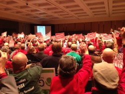 Opponents of the coal-export terminal, clad in red, raise their hands in support of a speaker at the Seattle hearing.