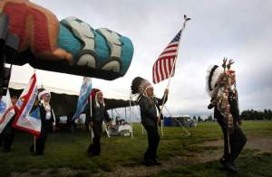 Members of the Yakama Warriors Association proceed out past a totem pole before a ceremony Sunday, Sept. 22, 2013, by the Confederated Tribes and Bands of the Yakama Nation blessing a Lummi Nation totem to raise awareness of inter-tribal opposition to the proposed international coal export hub on the Columbia River. (ANDY SAWYER/Yakima Herald-Republic)